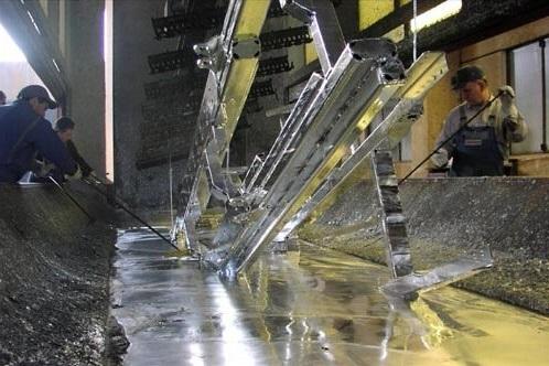 Процесс опускания стальной заготовки в цинковую ванну