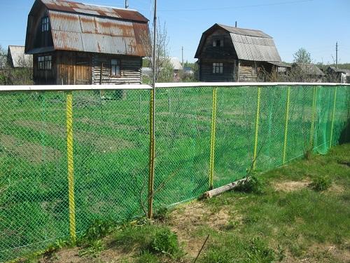 На фото забор из пластиковой сетки, возраст которого превышает 5 лет